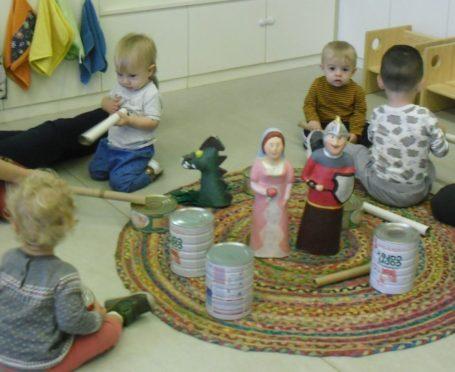 Una colla d'infants tocant timbals amb els gegants i el drac titelles