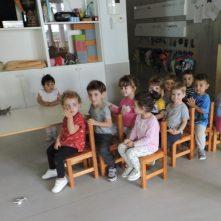 Els infants han col·locat les cadires en forma de tren i estan asseguts jugant