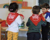 Dos infants d'esquena toquen el timbal. Porten el mocador vermell de festes