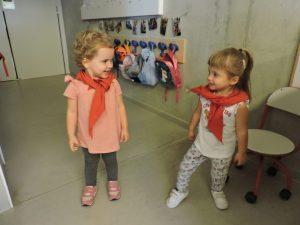 La Jana i la Emma de peu amb el mocador es miren i es fan un somriure una al costat de l'altra