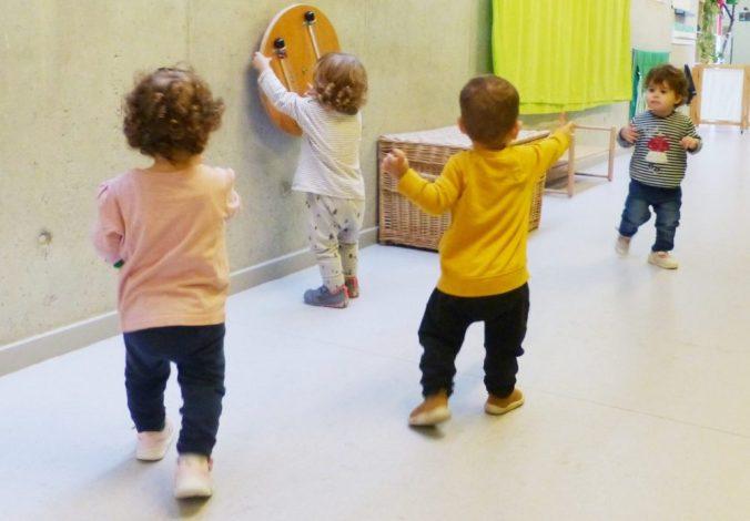 Tres nens voltant pel passadís de l'escola i un altre jugant a un joc a la paret.