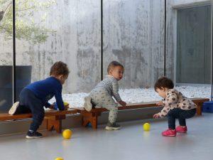 Hi ha dos nens gatejant per sobre d'un banc i una nena jugant amb pilotes.