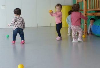 Hi ha quatre nenes voltant per la sala jugant amb pilotes petites.