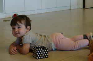 La Vega està estirada al terra panxa avall mirant els nens com juguen
