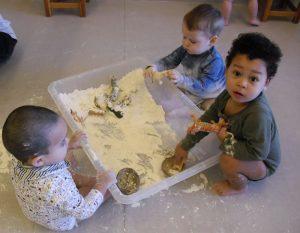una safata plena de farina i els infants agafen els animals
