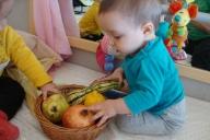 Dos infants descobrint la panera amb fruits de la tardor