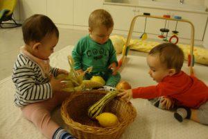 tres infants manipulant fruits de la tardor