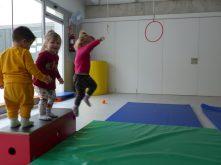 Una nena salta i dos infants estan drets damunt d'una caixa