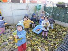Els infants de 2-3 anys juguen amb fulles al pati
