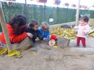 Tres infants amb la mestra han trobat el tió amagat entre uns troncs al pati.