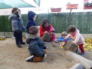 Sis infants amb la mestra miren el tió