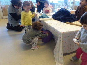 Una nena mira sota la taula per agafar els regals