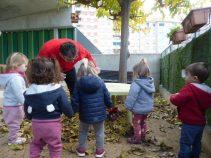 Els infants veuen el Tió envoltat de fulles