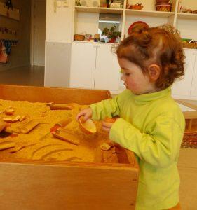 L'Alícia agafa el recipient fet amb la pell de la mandarina i se la mira