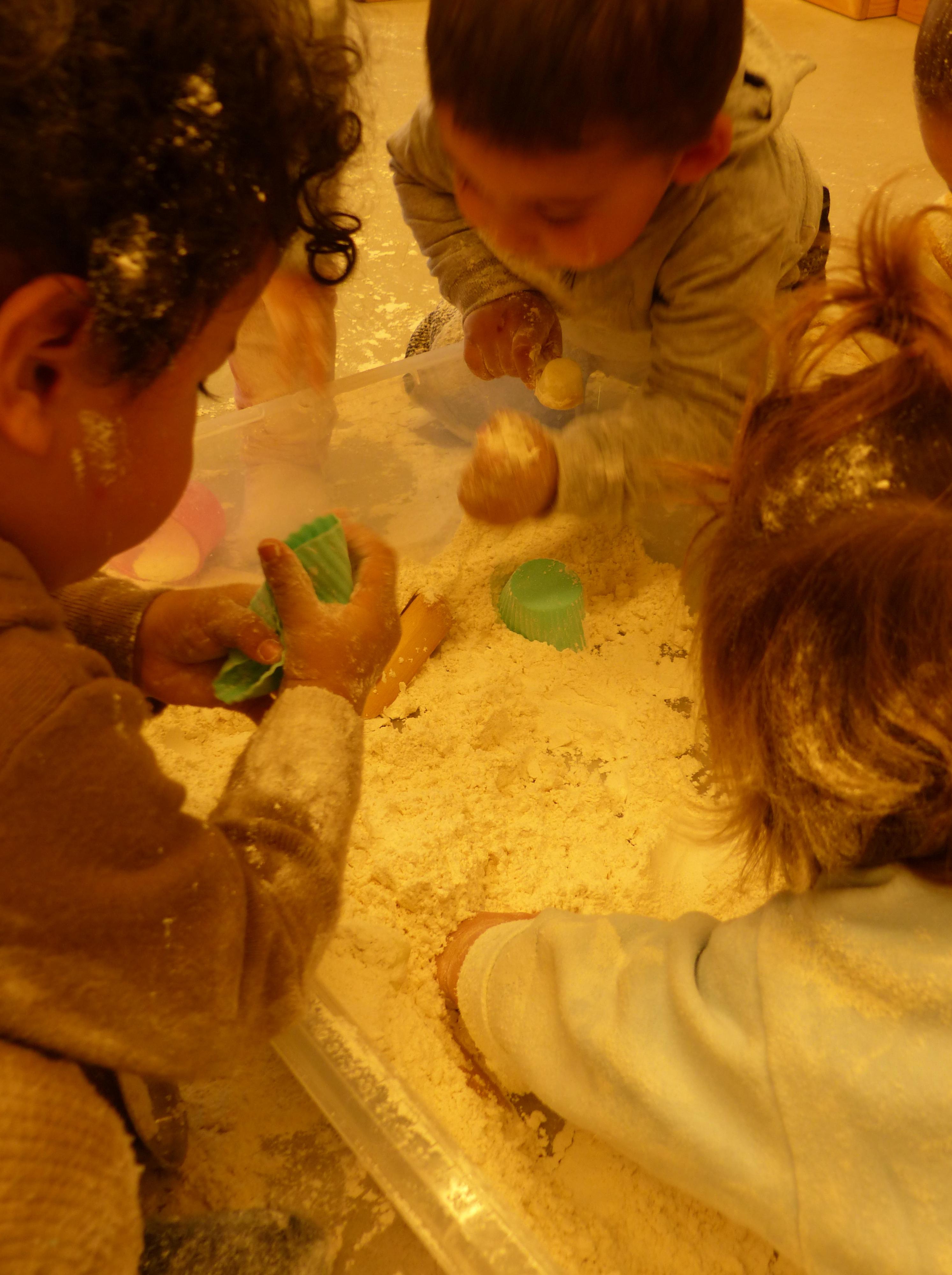 Hi ha quatre nens al voltant de la safata jugant amb farina.