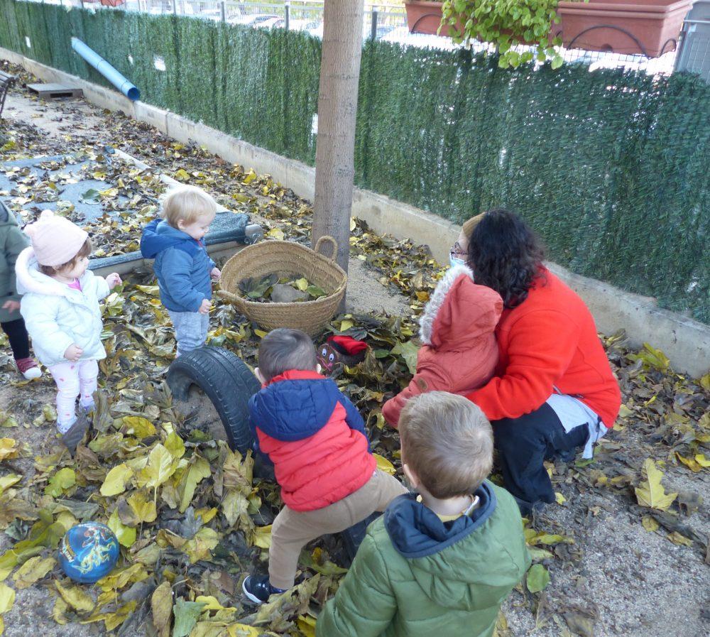 Cincs nens amb la seva educadora han sortit al jardí per anar a buscar el tió. de Nadal
