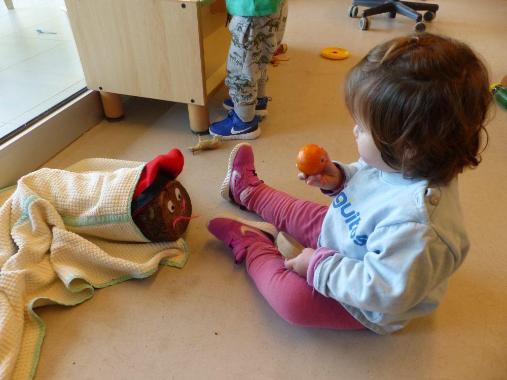 Una nena té una mandarina a la mà per donar-li al tió de Nadal.