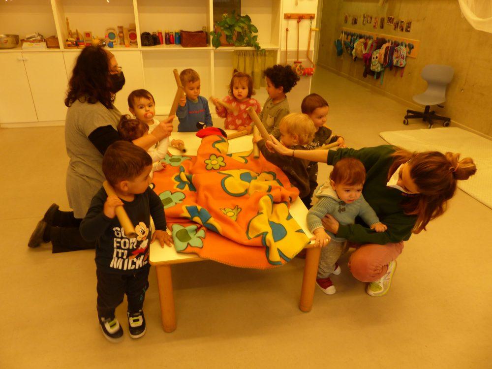 Els infants del grup dels timbalers piquen al tió mentre canten la seva cançó.
