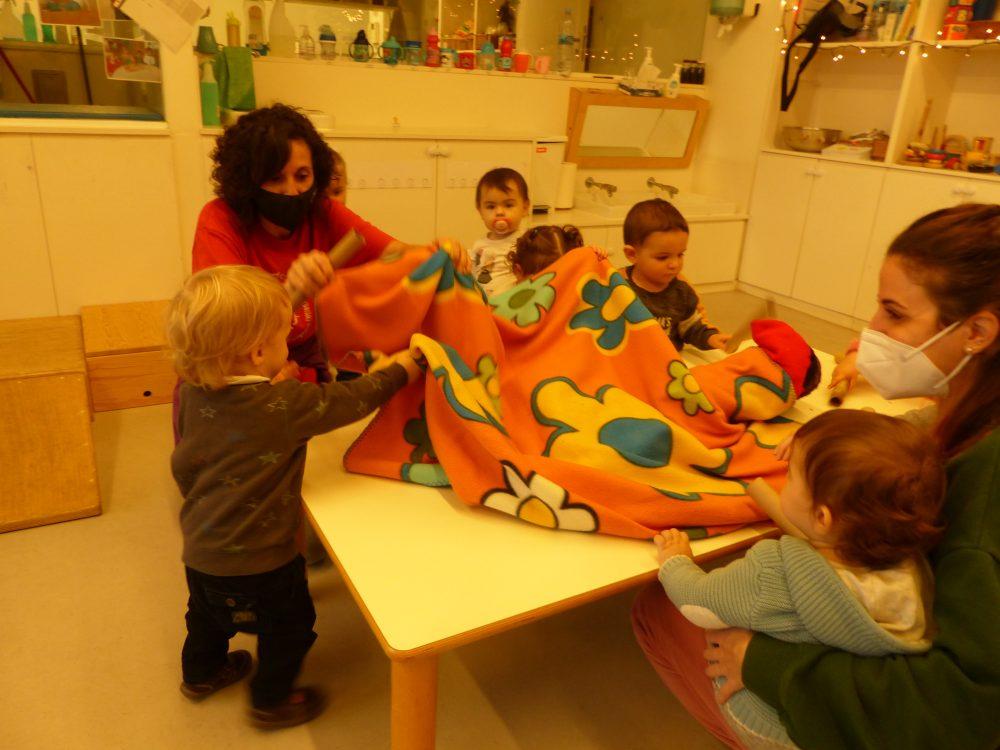 Un nen amb l'educadora està aixecant la manta del tió per veure si ha cagat.