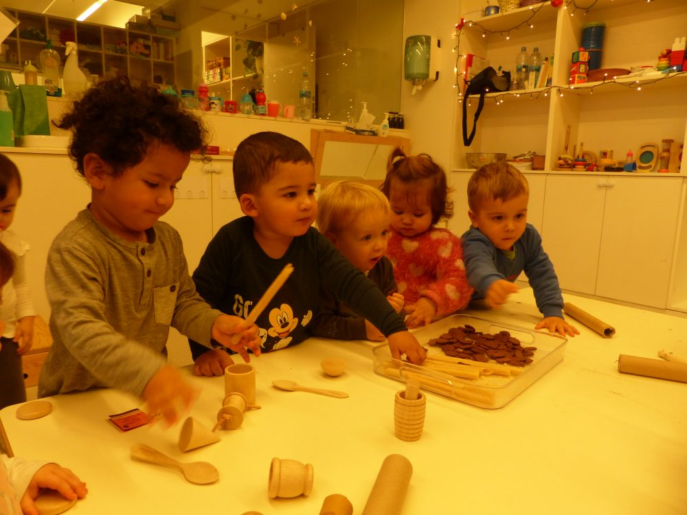Quatre infants estan menjant neules i galetes dins una safata.