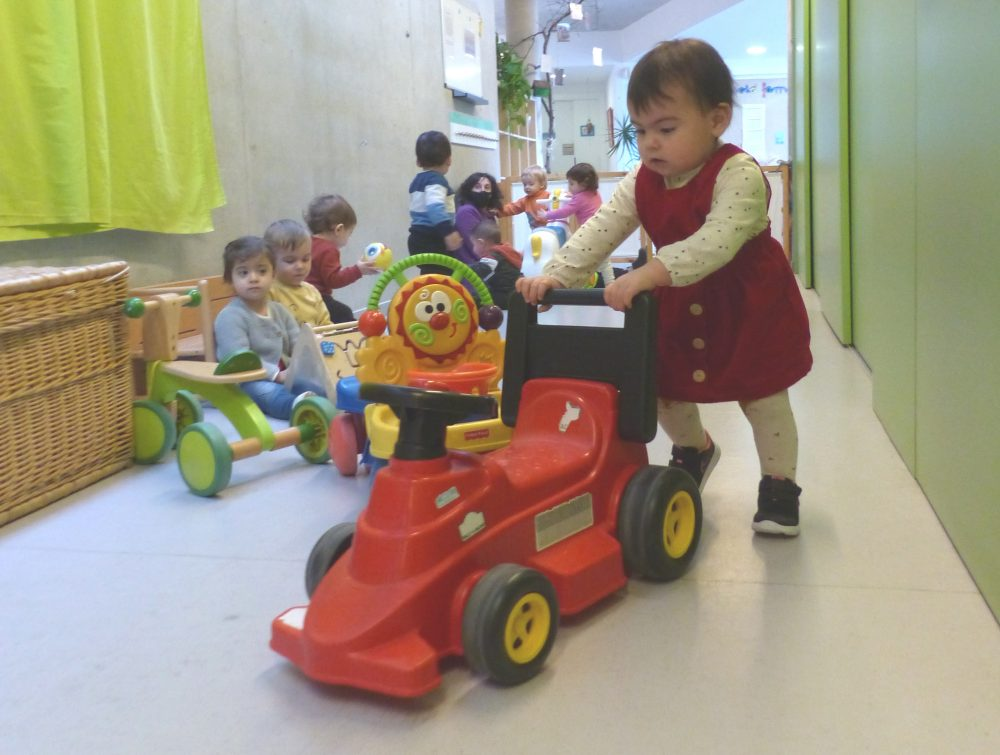 Un grupet d'infants juguen al passadís de l'escola