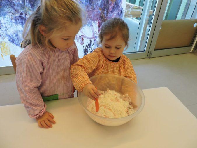 dos nenes remenen la massa de farina