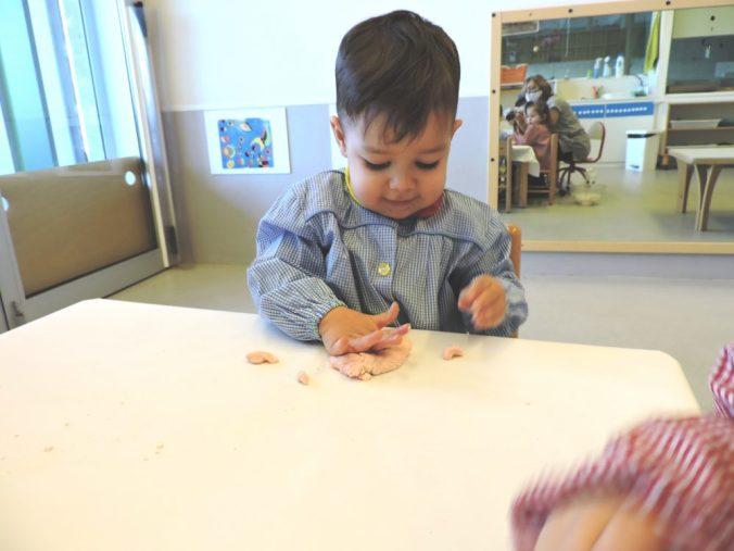 un nen xafa la massa amb les mans