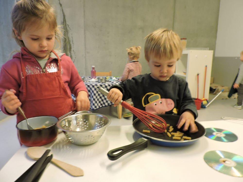 dos infants barregen aliments i cuinen