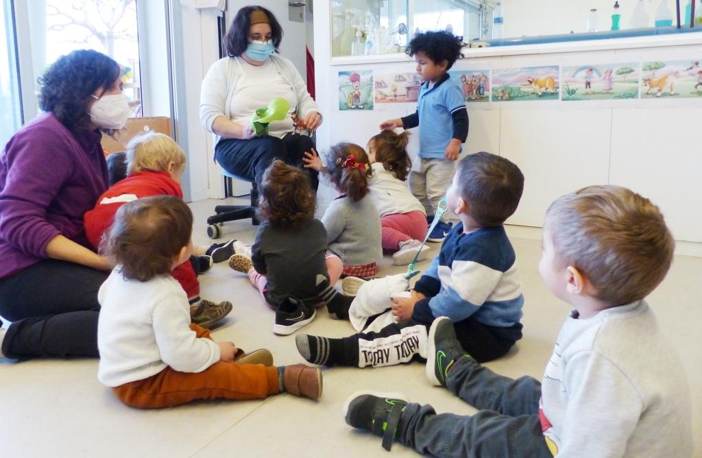 Els infants, asseguts al terra, escoltant el conte del patufet que explica la mestra.