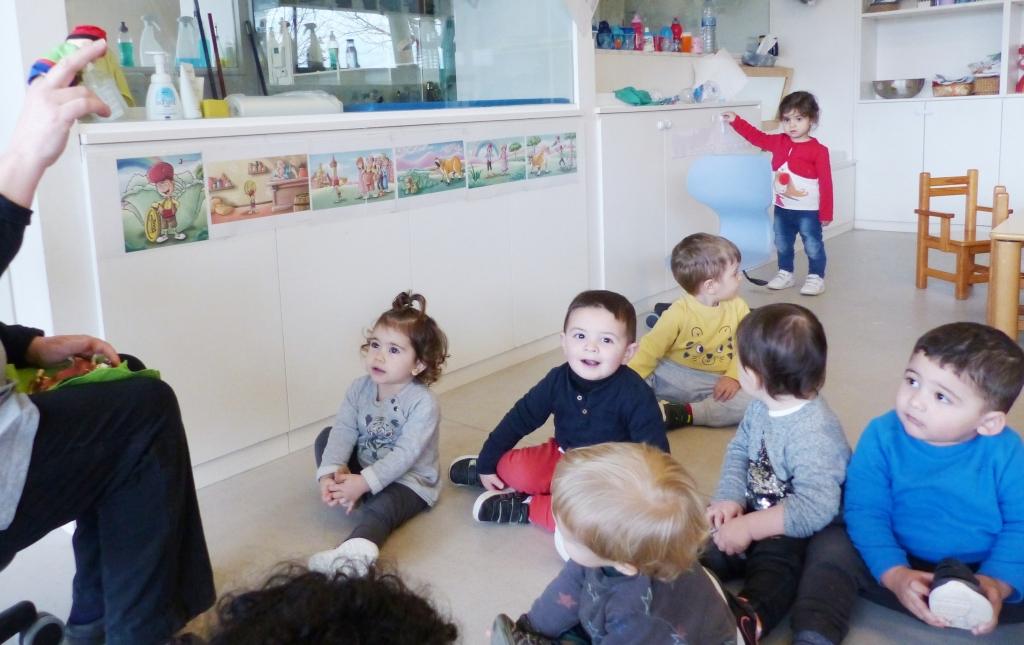 Un grup d'infants estan asseguts al terra escoltan el conte que explica la mestra