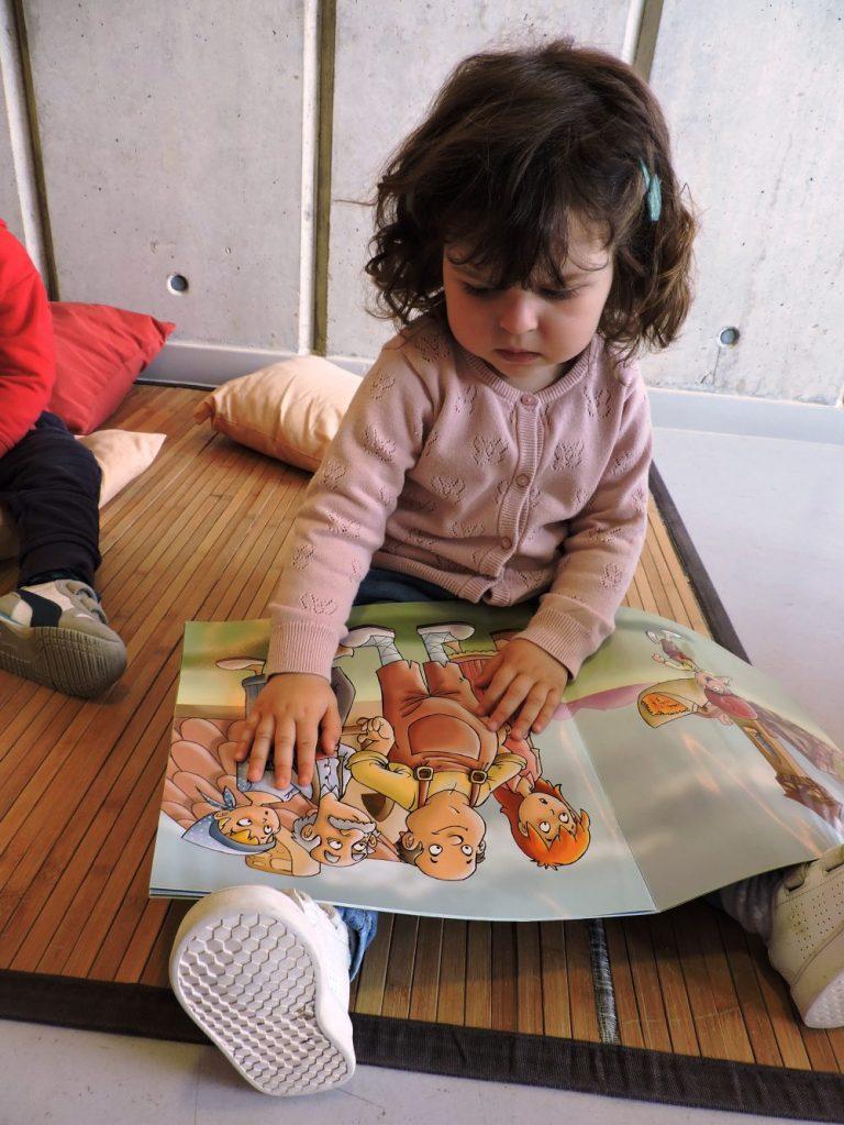 Una nena mirant el conte del Patufet