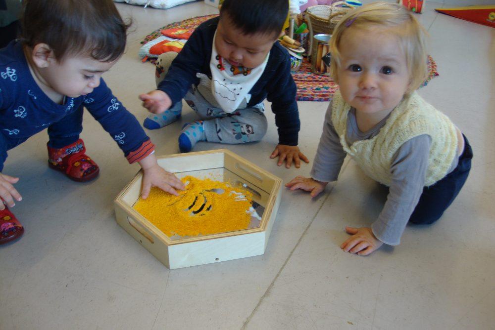 tres infants toquen la farina de mandarina per primer cop