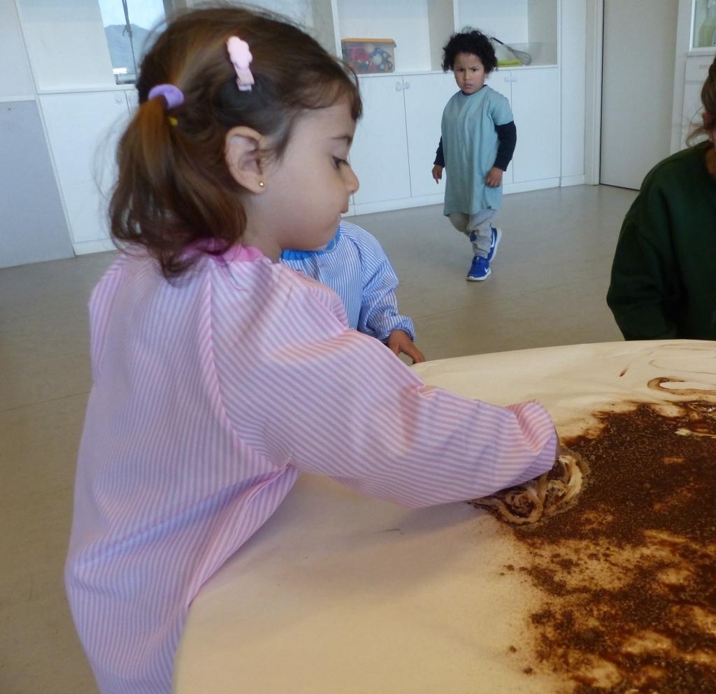 La Jana toca la xocolata que està sobre un paper blanc amb el dit