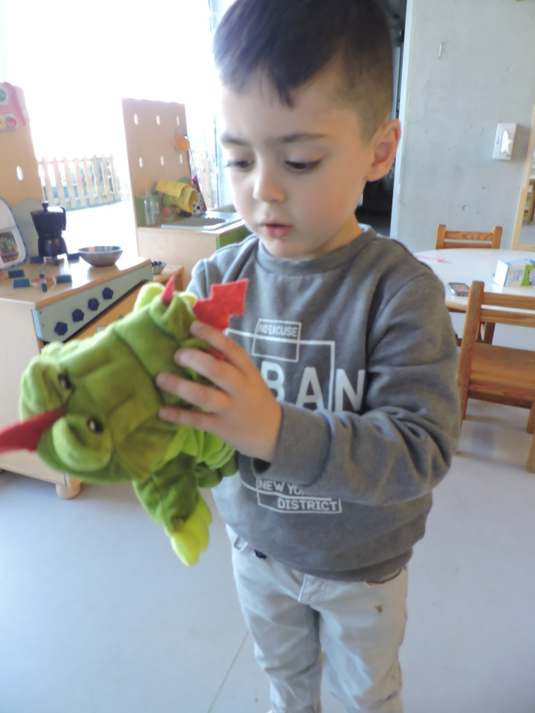 un infant juga amb el titella de drac