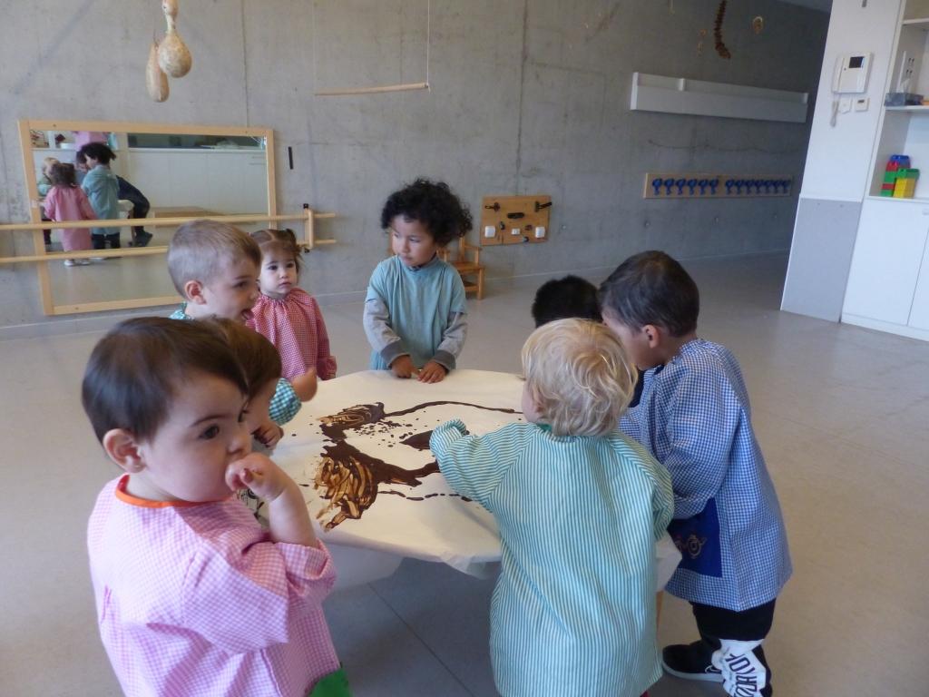 Uns quants infants al voltant de la taula tocant xocolata desfeta.