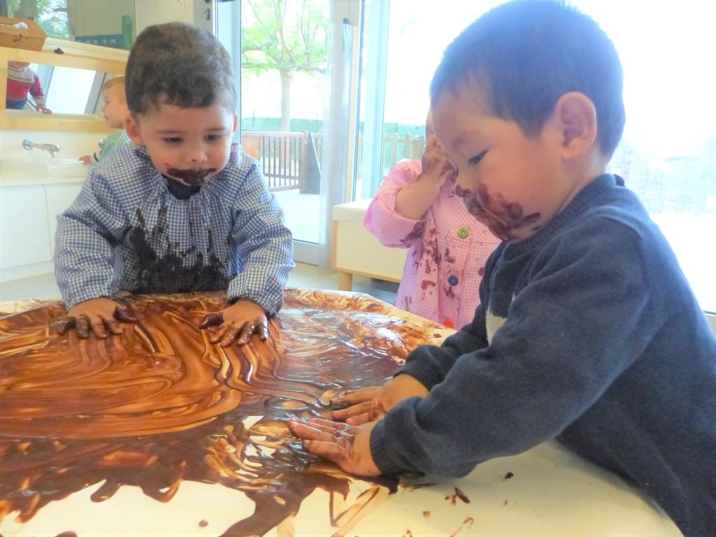 El Dylan i l'Alvaro tenen les dues mans a sobre la taula pintant amb la xocolata