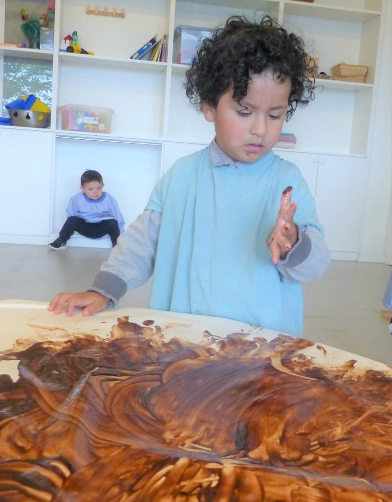 El Jorge es mira el dit perquè té xocolata.