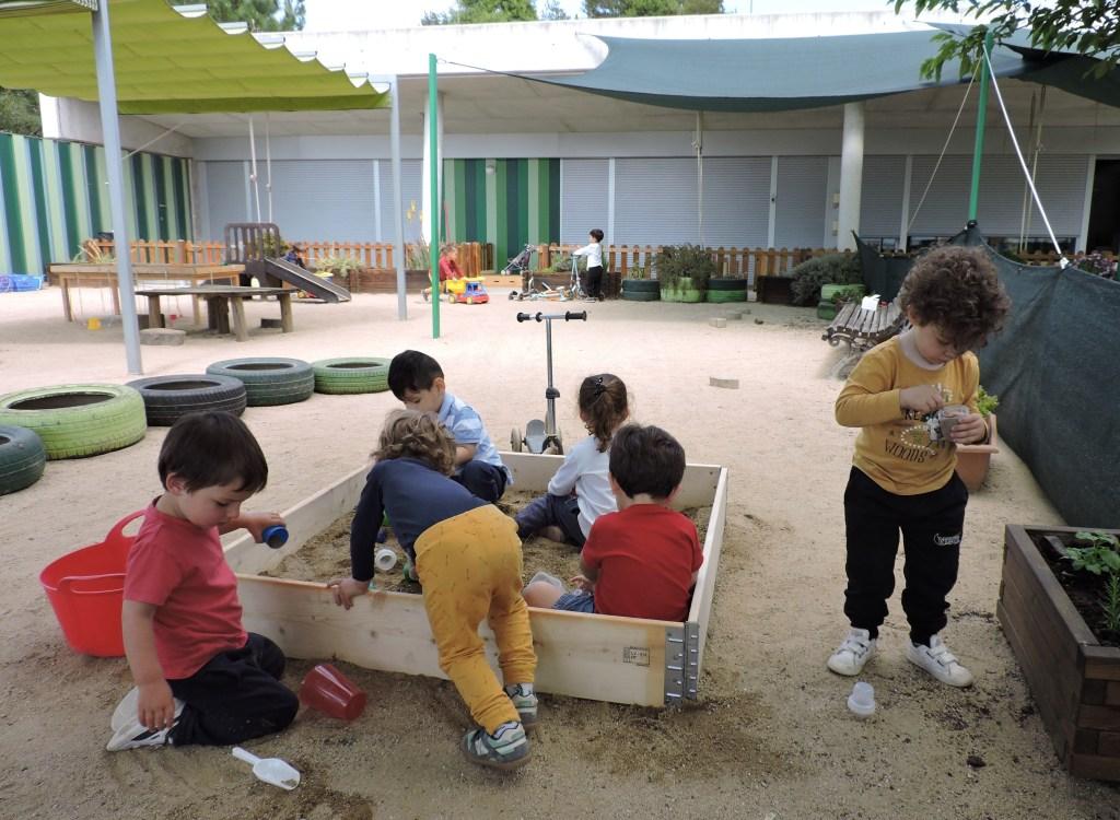 Un grupet d'infants juguen al jardí a la tarda