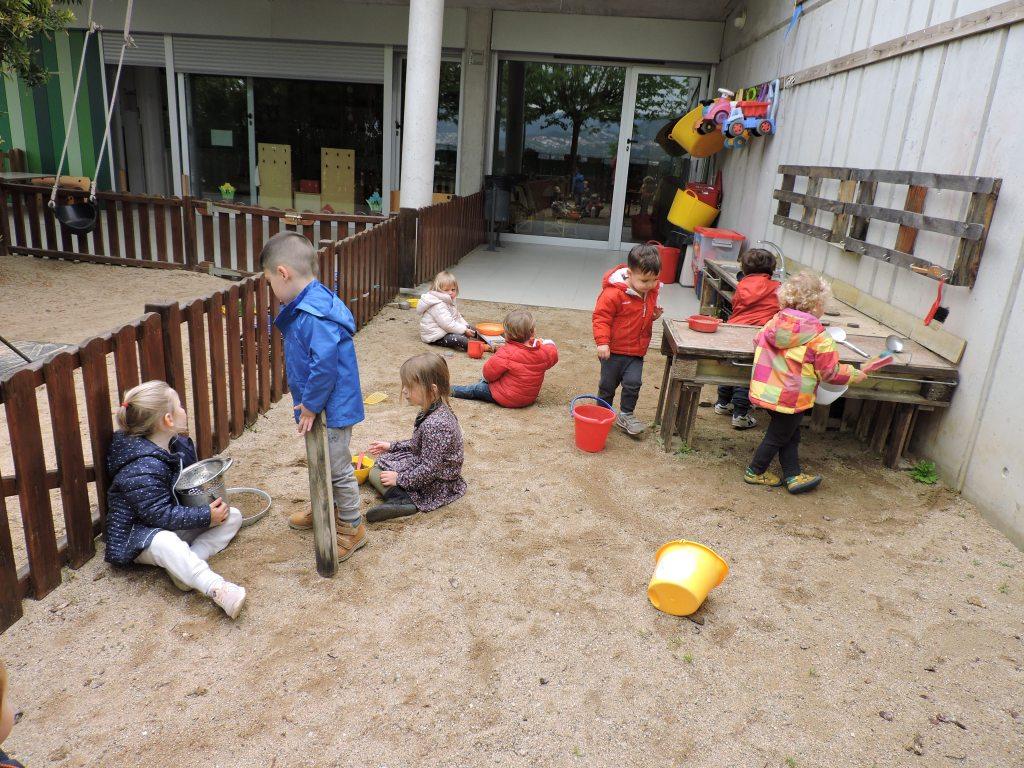 Un grup d'infants estan jugant a la cuineta de l'exterior