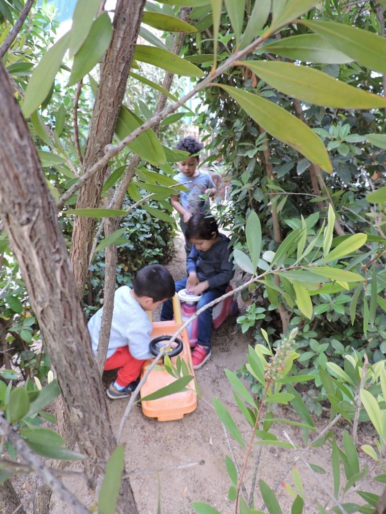 tres infants s'amaguen jugant al laberint