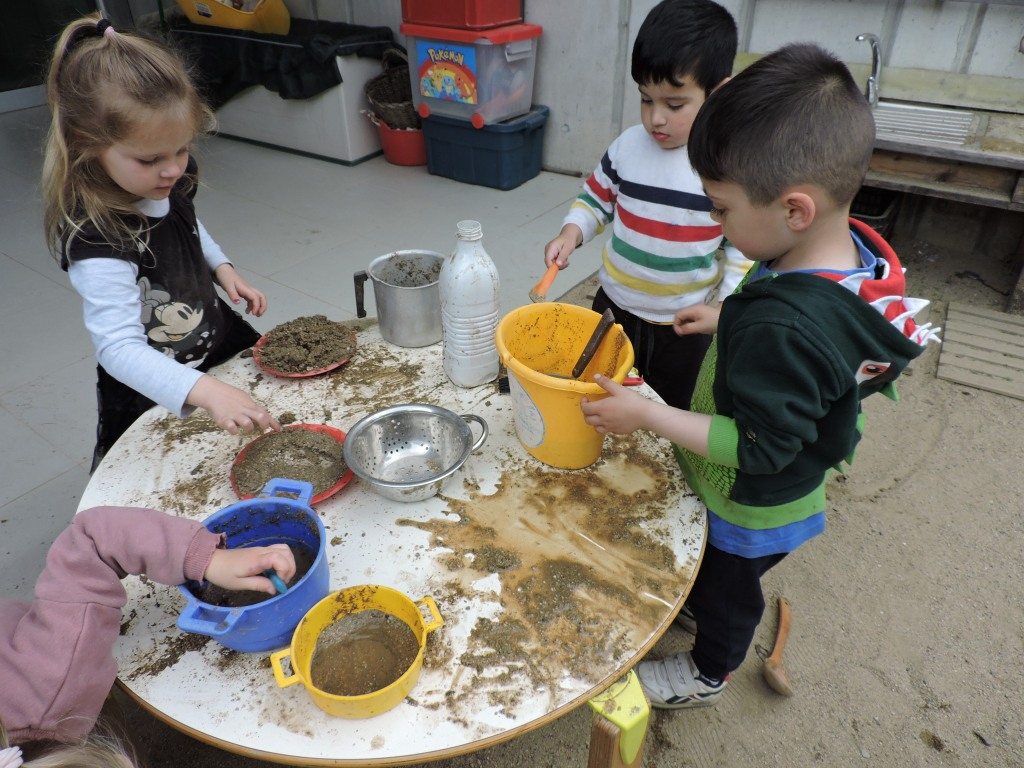 Juguen a la cuineta del pati amb terra i aigua