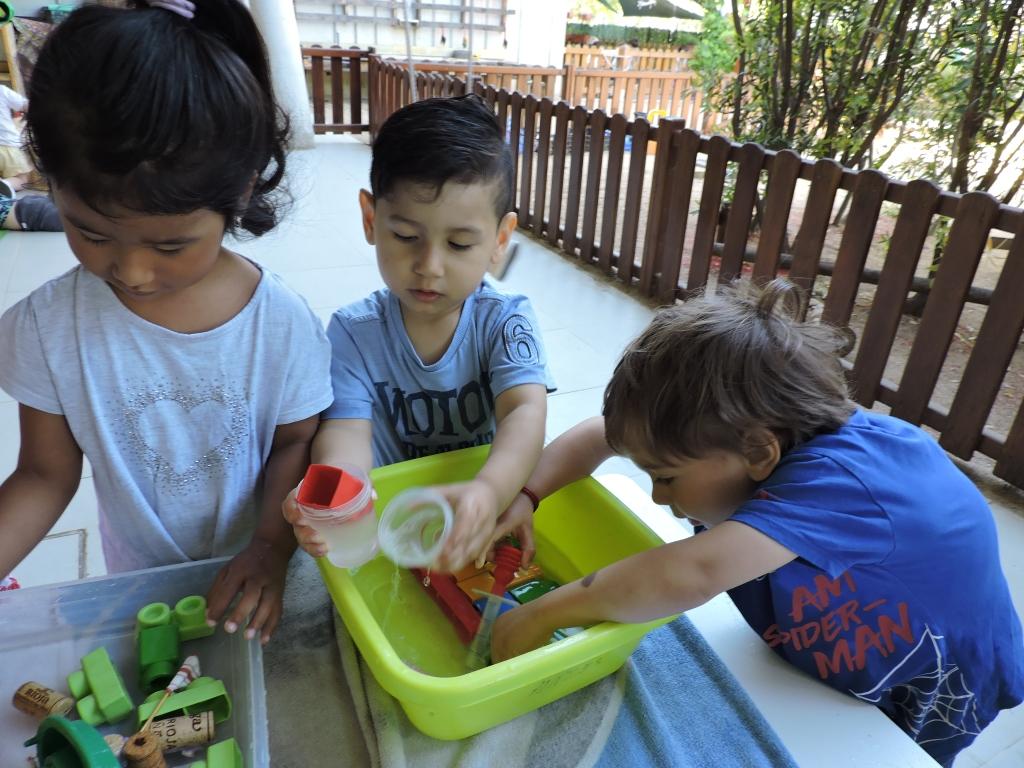 Tres infants juguen amb pots i aigua