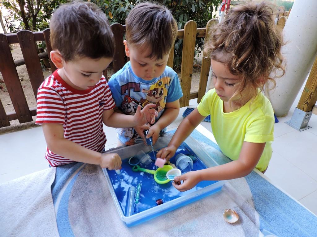 Dos nens i una nena juguen amb aigua de color blau